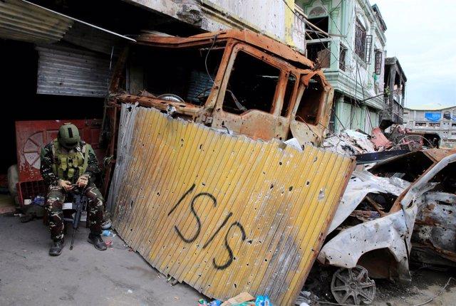 Soldado filipino en la ciudad de Marawi junto a una pintada de Estado Islámico