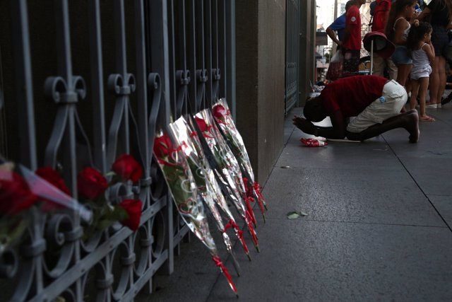 A man reacts next to flowers after a shooting at Catholic cathedral in Campinas,