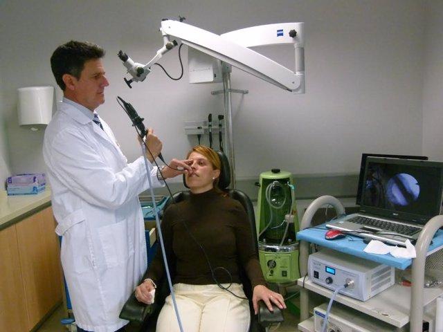 Un médico le realiza a una mujer un diagnóstico de la voz