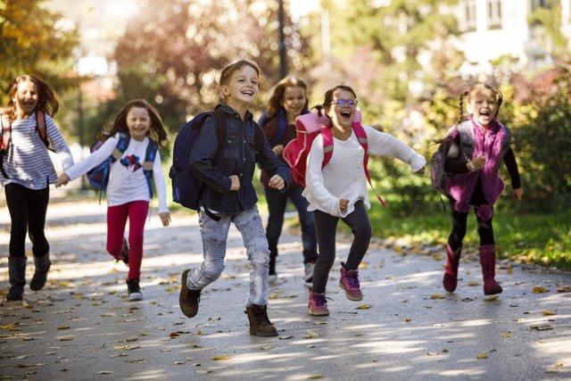 Niños, escolares con mochila, corriendo, jugando, yendo al colegio