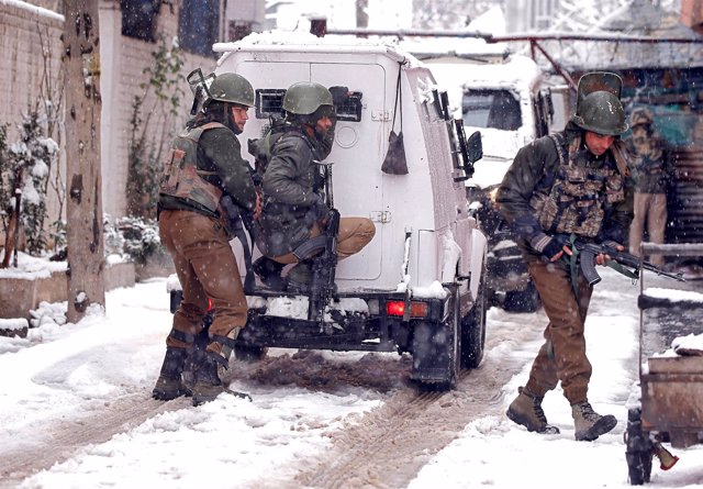 Policías indios toman sus posiciones cerca del lugar de un tiroteo en Cachemira