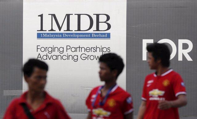 Hombres pasando ante un cartel del fondo 1MDB en Kuala Lumpur