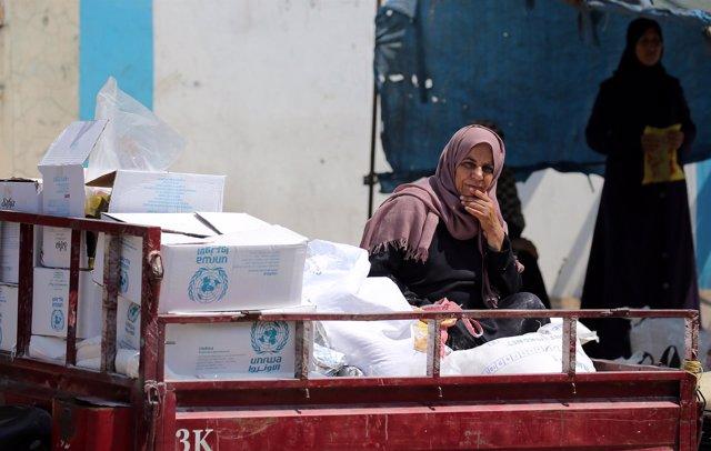 Una mujer palestina en un vehículo con ayuda de la UNRWA