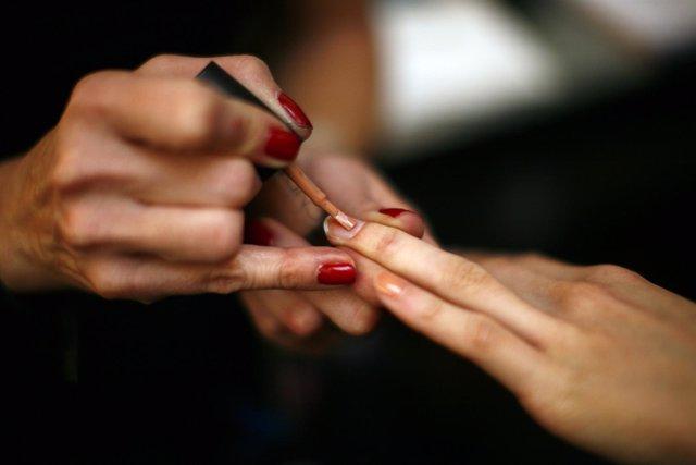 Una persona pintándose las uñas