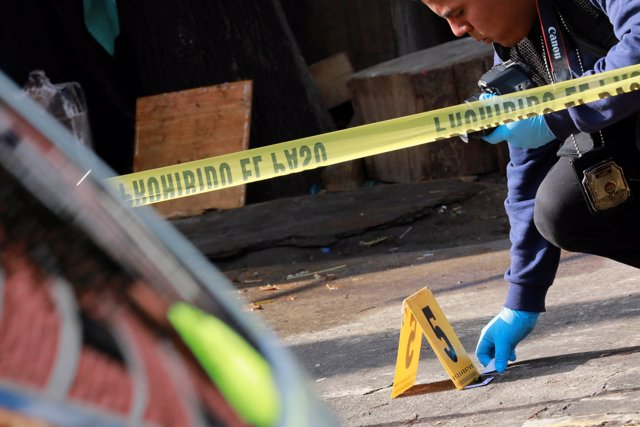 A forensic technician works at a crime scene where two men were gunned down by u