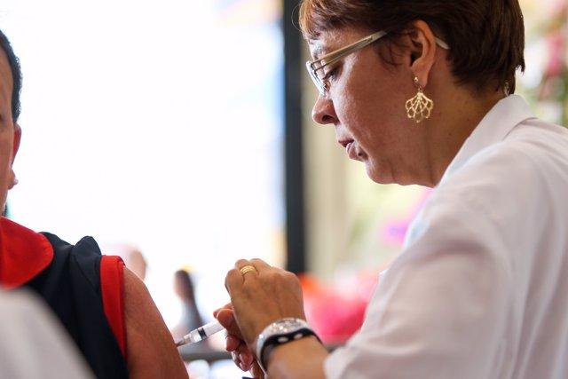 Una enfermera vacuna de la gripe