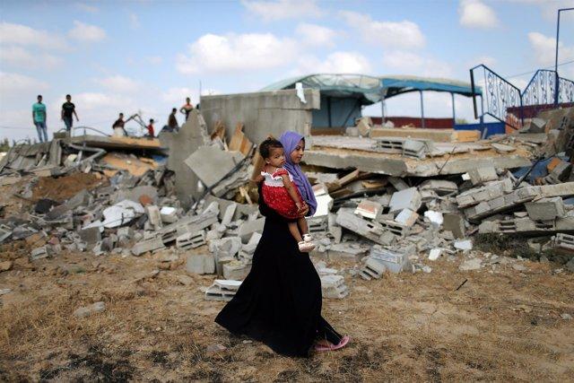 Una mujer pasea con su hijo por una zona bombardeada de Gaza