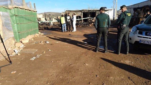 Agentes vigilan la zona de chabolas afectada por el incendio en Níjar (Almería)