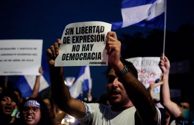 Manifestante en Nicaragua con cartel Sin libertad de expresión no hay democracia