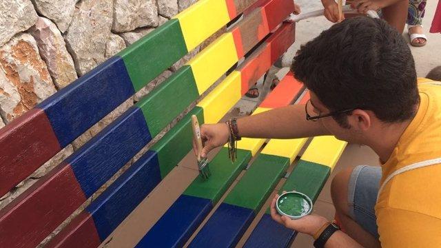 Un niño pintando un banco de los colores LGTBI