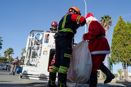 Bomberos ayudan a Papá Noel a entrar por la ventana del Hospital Juan Ramón Jiménez de Huelva para visitar a pacientes