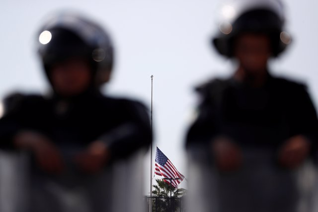 A U.S. Flag is lowered in the U.S. Consulate as Mexican riot police officers sta