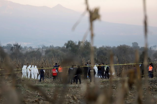 Forensic technicians and rescue personnel stand at the scene where the helicopte