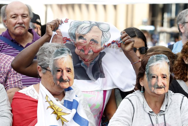 People wearing masks depicting Uruguay's President Jose Mujica participate in a