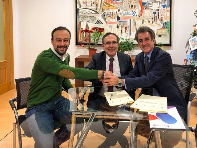 Consejero y alcalde firman el protoco acompañados por el teniente de alcalde