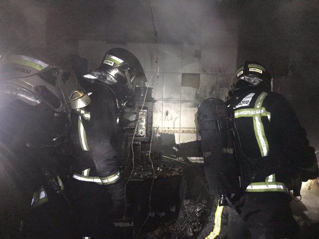 Bomberos de la Comunidad de Madrid trabajan en el incendio de una vivienda