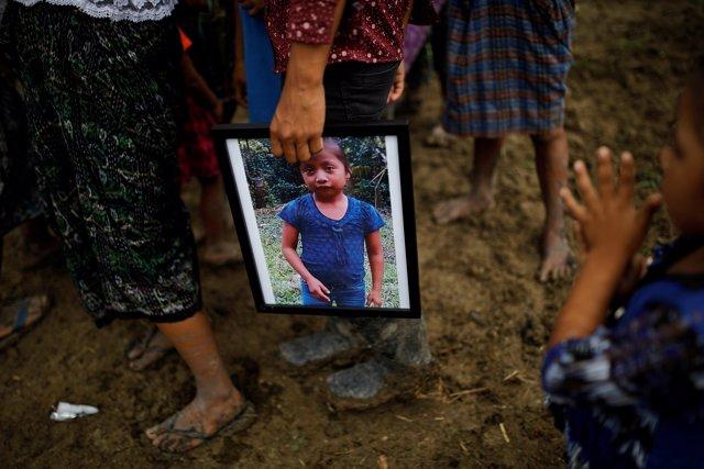 Un hombre sostiene una fotografía de Jakelin Caal durante su funeral