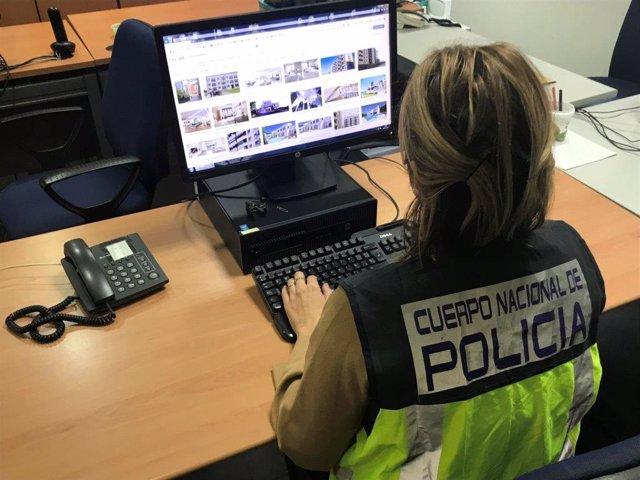 Agente de la Policía realizando una búsqueda de viviendas utilizadas para estafa