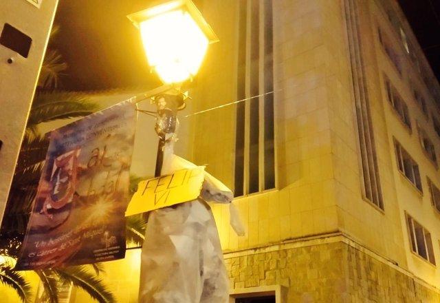 Arran cuelga un monigote con un cartel del Rey en una farolaii