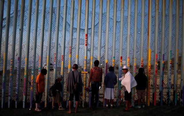Migrants, part of a caravan of thousands from Central America, try to reach the