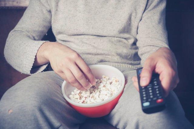 Hombre con el mando de la tele viendo una película y comiendo palomitas