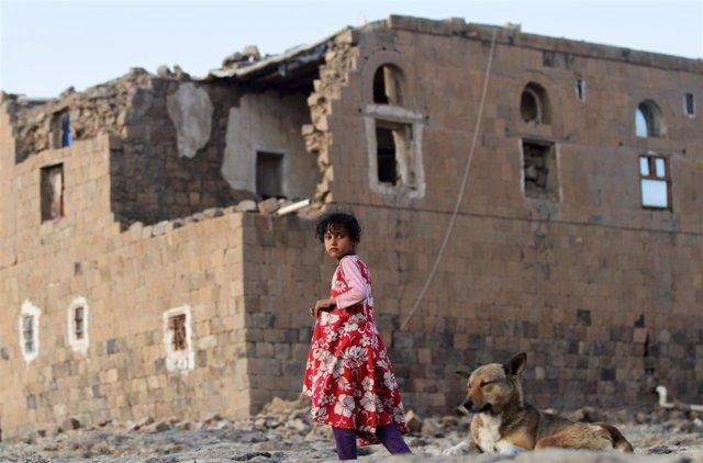 Una niña junto a una casa destruida en Saná