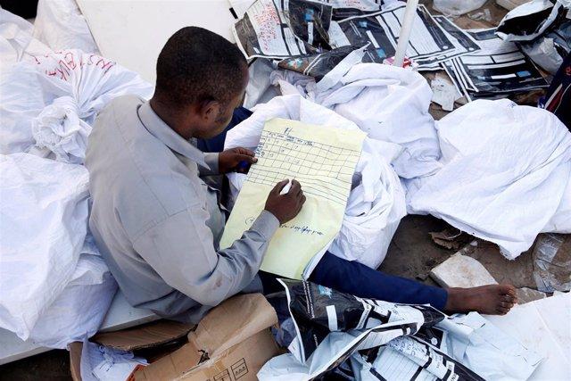 Un hombre examina material electoral en República Democrática del Congo