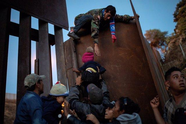 Migrantes tratan de saltar la valla en la frontera entre México y EEUU