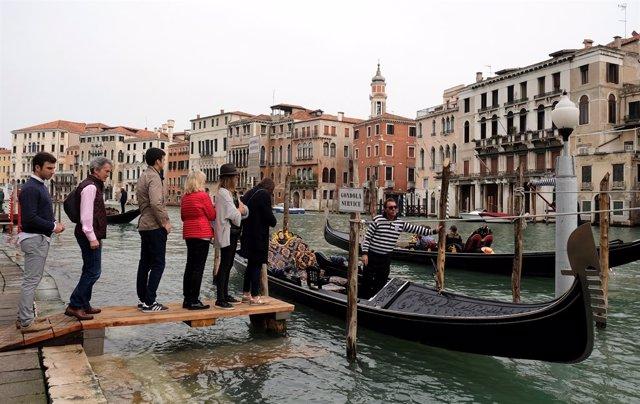 Turistas suben a una góndola en Venecia
