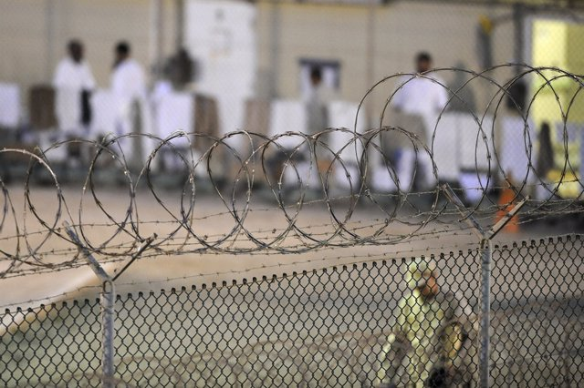 A Navy guard patrols Camp Delta?s detainee recreation yard during the early morn