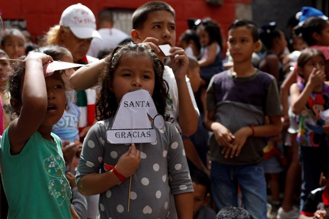 """A girl holds a sign, which reads: """"Thanks, Santa"""", during the """"Santa en las call"""