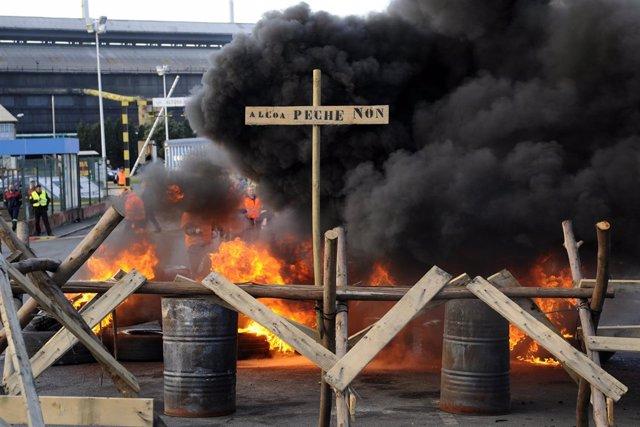 Los trabajadores de Alcoa queman neumáticos horas antes de iniciar la huelga