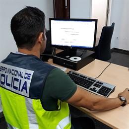 Policía Nacional frente a una pantalla de ordenador
