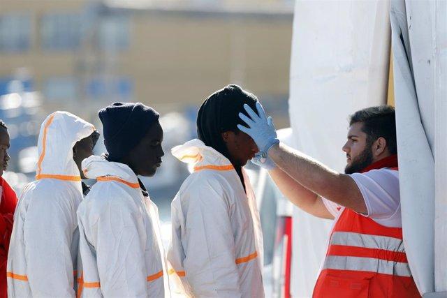 Un miembro de Cruz Roja atiende a inmigrantes llegados al puerto de Málaga