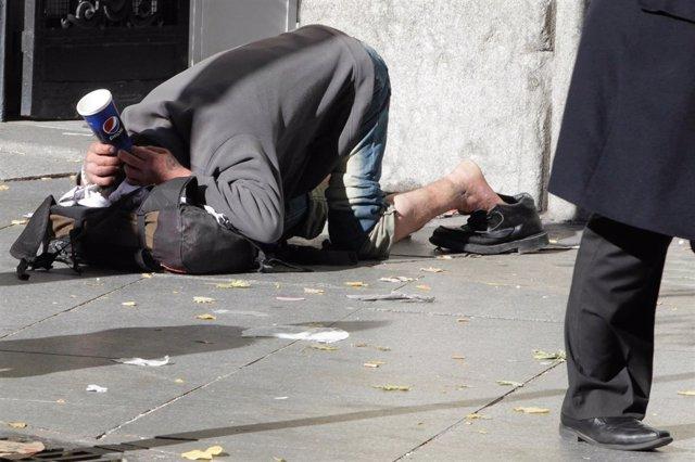 Un persona pidiendo en la calle