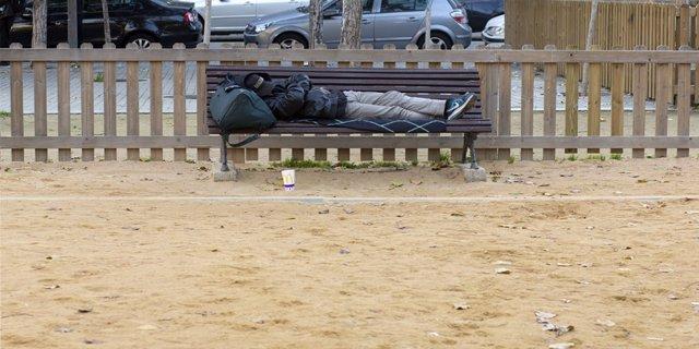 Una persona duerme en un banco en Barcelona