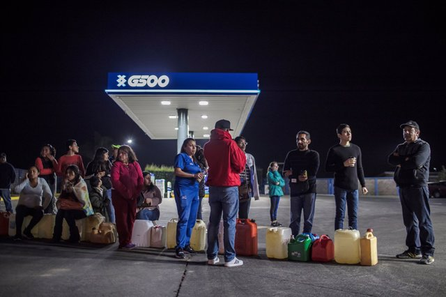 People queue to buy gasoline at a gas station after an offensive by Mexico's gov