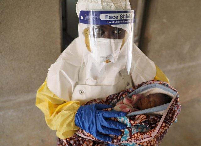 Trabajador sanitario con un niño posiblemente enfermo de ébola