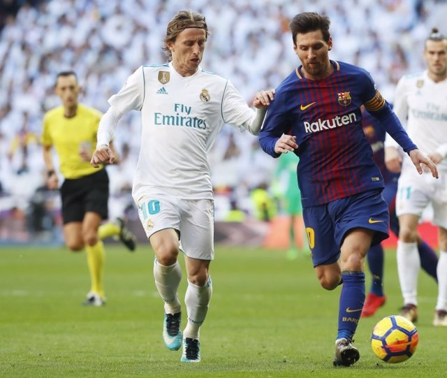 Luka Modric y Leo Messi disputan un balón en el clásico