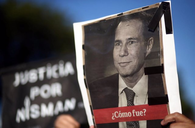A woman holds up a photo of late state prosecutor Alberto Nisman, lead investiga