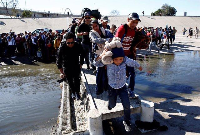 Migrantes cruzan el río en Tijuana para llegar a la frontera con EEUU