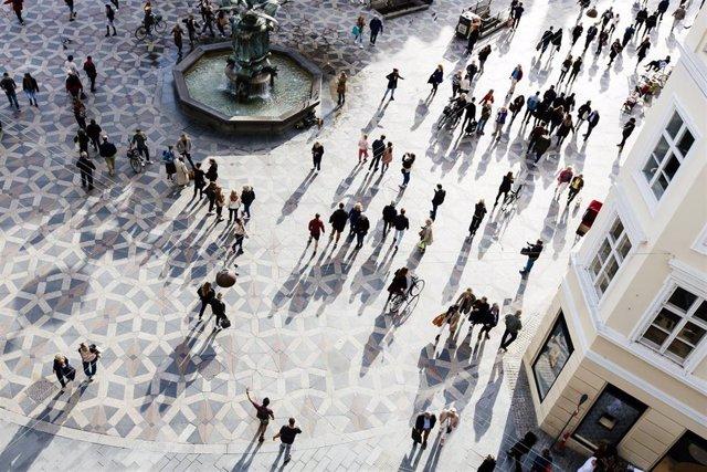 Gente paseando en la plaza de una ciudad