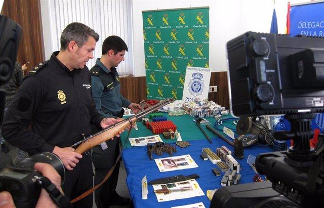 Agentes Policía N. Y Guardia Civil sujetando armas
