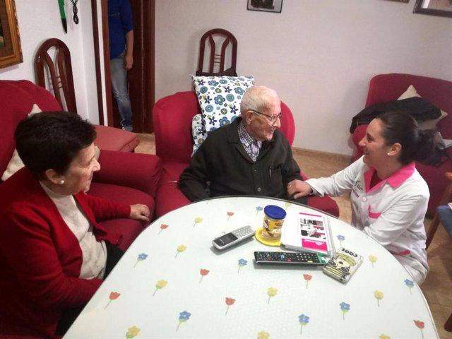 Una trabajadora del servicio de ayuda a domicilio conversa con dos usuarios.
