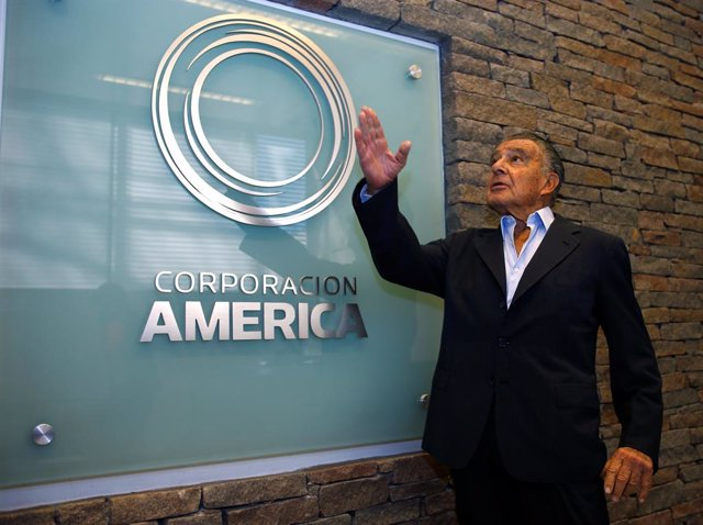 Argentine business magnate Eduardo Eurnekian poses next to a logo of his company