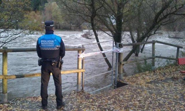 Un policía municpal vigilando la crecida del río Arga en Pamplona
