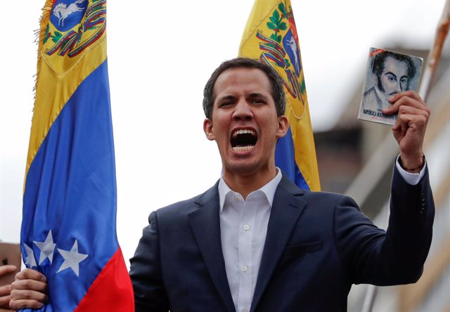 Juan Guaido, President of Venezuela's National Assembly, holds a copy of Venezue