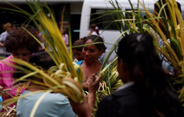 A woman buys crosses made out of palm fronds for the oncoming Palm Sunday in Teg
