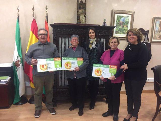 Carmen Belén López y Lourdes Ramos con los ganadores de los cheques regalo.