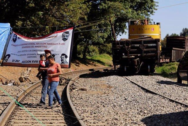 Residentes cruzan las vías de tren bloqueadas por las protestas de profesores